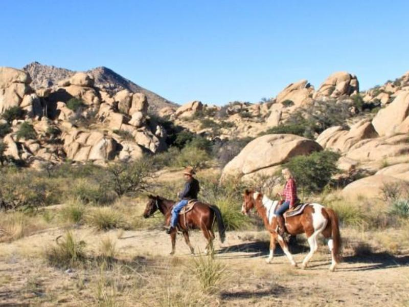 Horseback riding amidst Arizona's gigantic boulders piled high in startling formations